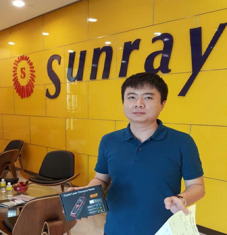 Sunray Woodcraft Construction Pte Ltd's representative receiving the free gift of laser distance measure with online purchase.