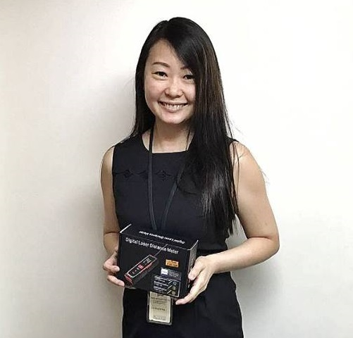 Swee Builders Pte Ltd's representative receiving the free gift of laser distance measure.