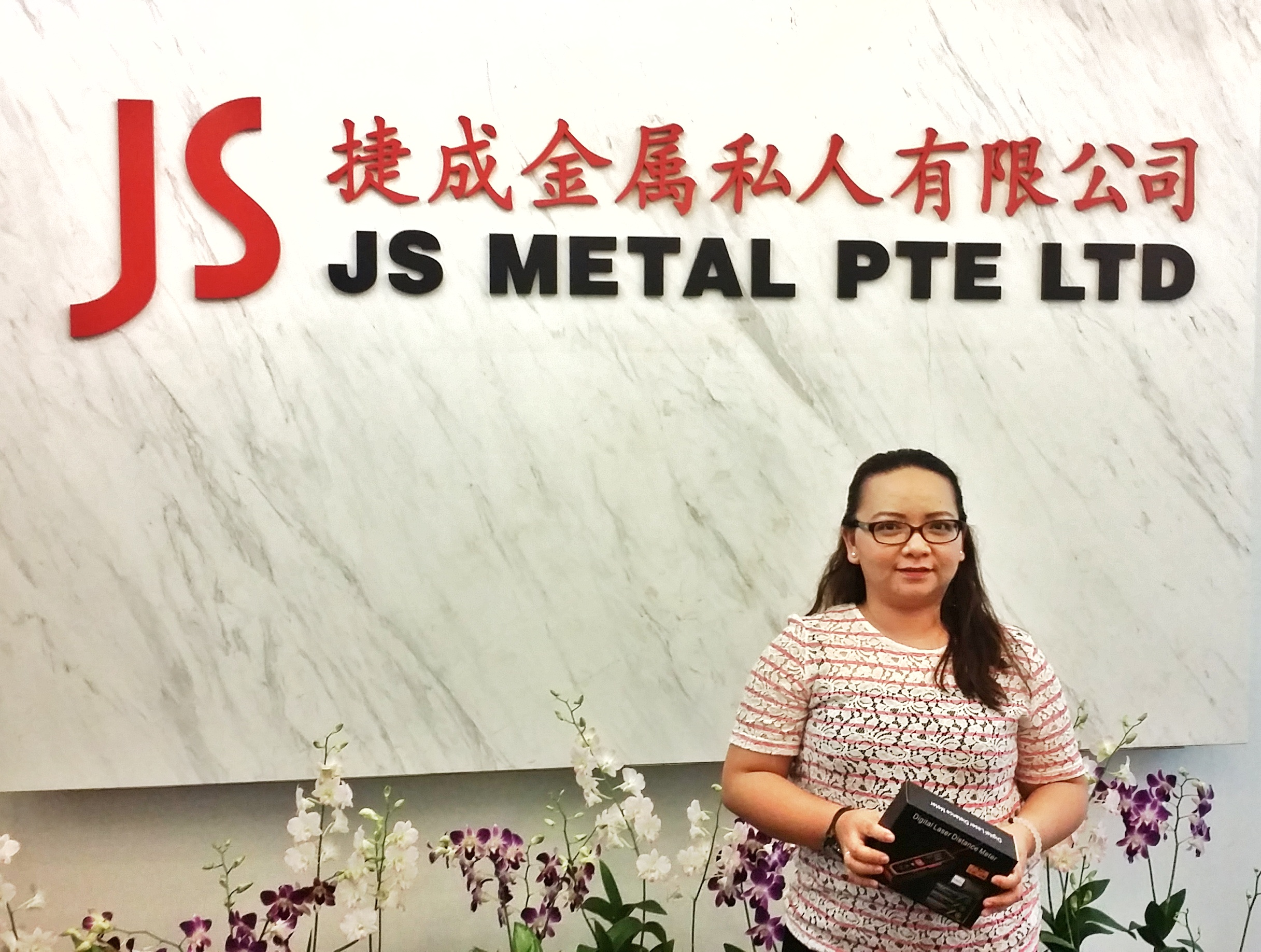JS Metal Pte Ltd representative receiving the free gift of laser distance measure.