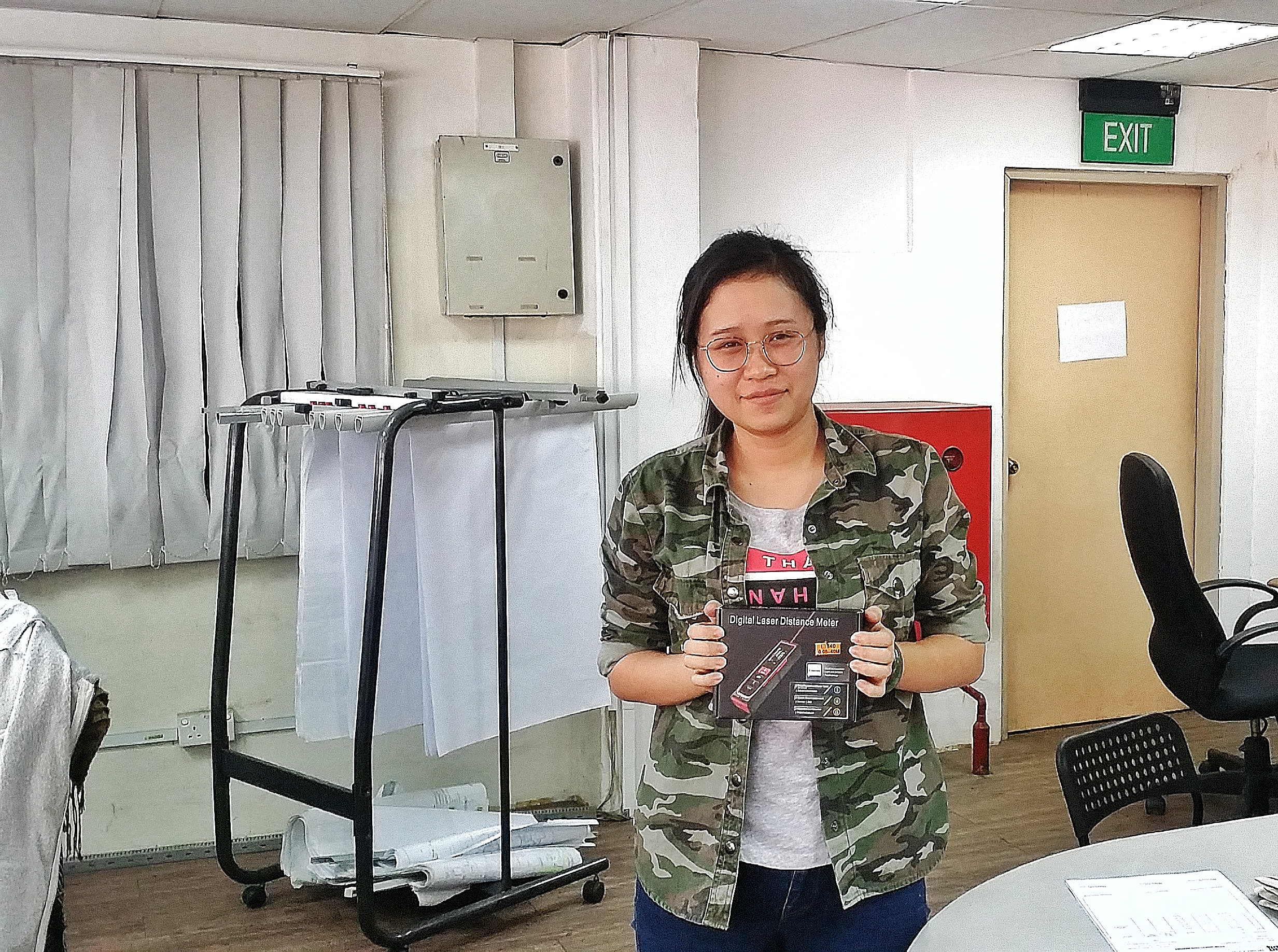W Y Steel's representative receiving the free gift of laser distance measure.