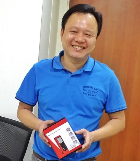 Hon Builder Pte Ltd's representative receiving the free gift of laser distance measure.